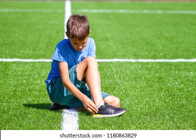 Boy injured his leg. Child sitting on the grass at soccer football stadium