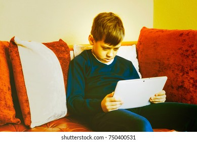 Boy interested viewed video on tablet pc sitting