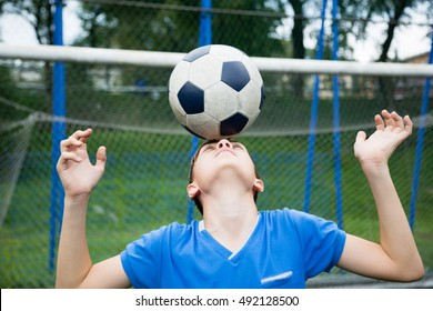 Boy juggling a soccer ball on stadium
