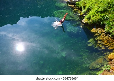 Boy jump to the clear blue lake in wild nature covered in green mountains