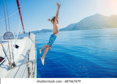 Boy jump in sea of sailing yacht on summer cruise. Travel adventure, yachting with child on family vacation.