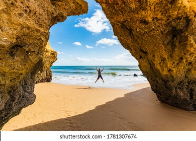 Boy jumping at cliff with a hole on beach
