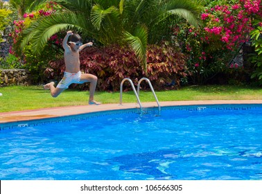 boy jumping in cool water of swimming pool