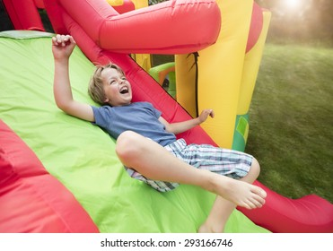Boy jumping down the slide on an inflatable bouncy castle