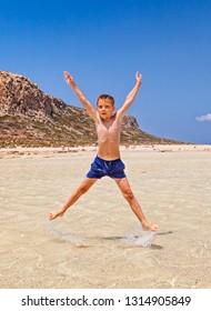 Boy jumping high on the beach. Balos bay, Crete, Greece.