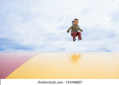 boy jumping high on a outdoor trampoline