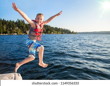 Boy jumping into a beautiful mountain lake. Having fun on a summer vacation. Having fun on a summer vacation. Excited expression on his face and arms raised high