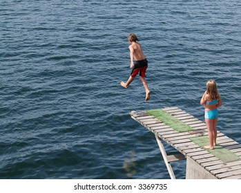 Boy jumping into the sea, and his sister is watching