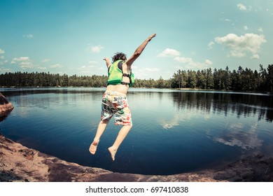 A boy jumping into water from a rock.