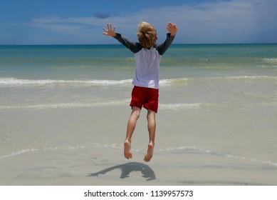 Boy jumping with joy on a Florida beach