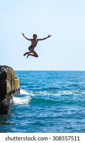 Boy jumping off cliff into the sea. Summer fun lifestyle