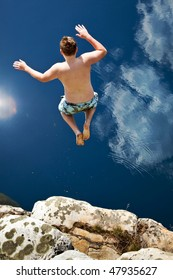 Boy Jumping Off Cliff Into Blue Water