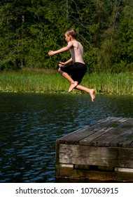Boy jumping off dock into a lake