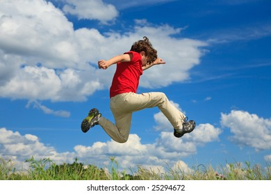 Boy jumping on green meadow