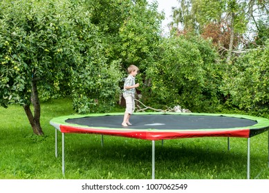 Boy is jumping on a trampoline in the garden