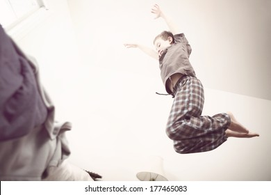 Boy jumping onto a bed