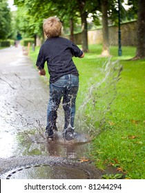 boy is jumping in the puddle