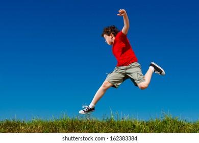 Boy jumping, running against blue sky