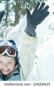 Boy jumping in snow, arms raised, smiling