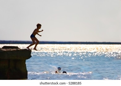 The boy jumping in water from a pier