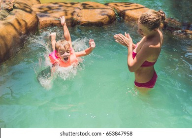 A boy jumps into the water in a pool.