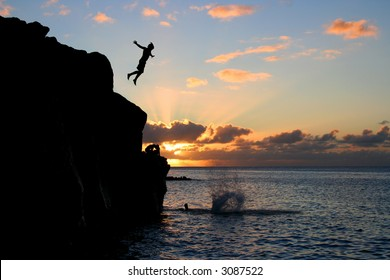 Boy jumps off a cliff into the ocean at Waimea Bay in Hawaii at sunset.