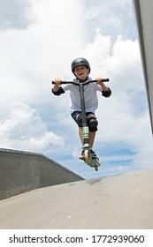 Der Junge springt auf einen Roller. Ein süßer kleiner Junge fährt einen Roller in einem Skatepark. Ein junger Anfänger verbringt Freizeit im Extremsport.