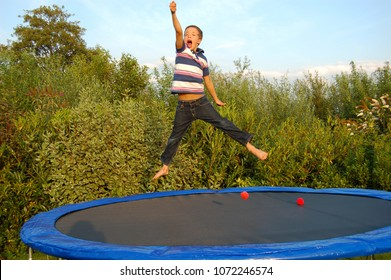 Boy jumps on a trampoline and adopts the championship posture.