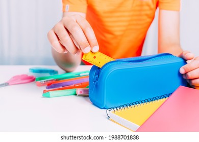 Boy keeping inside his blue pencil case all a small ruler and pencils, pencils, scissors, etc. Colorful notebooks on white table. Back to school concept