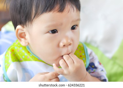a boy keeps finger in the mouth