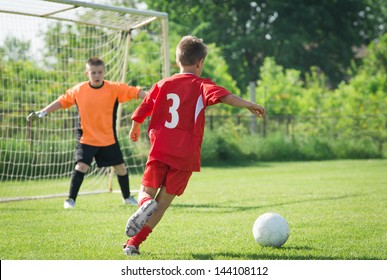 boy kicking a ball at goal