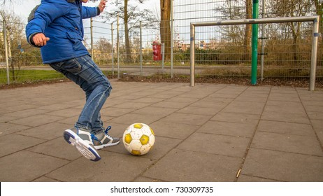 Boy kicking football while shooting on goal on urban soccer field with paving