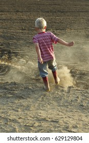 A boy kicking into the soil of his feet in the field