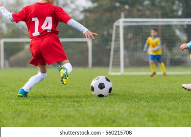 Boy kicking soccer ball on sports field