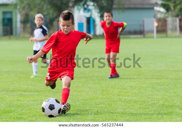 Boy kicking soccer ball on sports field