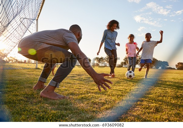 A boy kicks a football during a game with his family