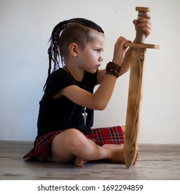a boy in a kilt sits with a sword, looks forward.