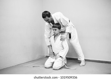 A boy in a kimono has an aikido training with a coach