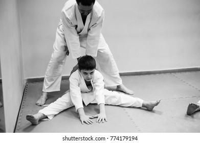A boy in a kimono has an aikido training with a coach