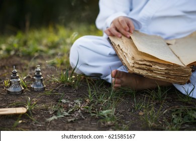 Boy in a kimono sits in a  yoga lotus position meditating, reading old open book of wisdom and there are a number  Tibetan bells  and burn incense at meadow