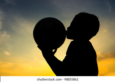 Boy kiss the ball during sunset
