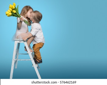 Boy Kisses Girl and Gives Flowers. Copy Space
