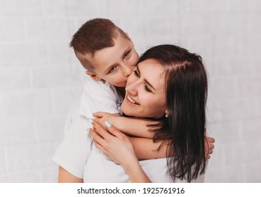 Boy kisses his mom and hugs on white background