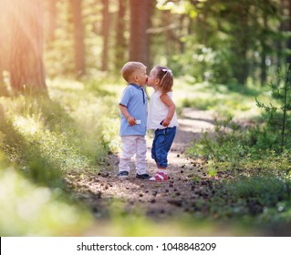 Boy and boy kissing in the forest in summer