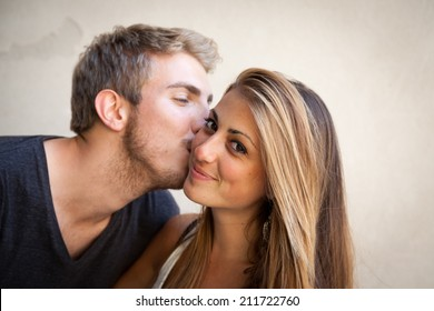 Boy kissing his girlfriend on the cheek