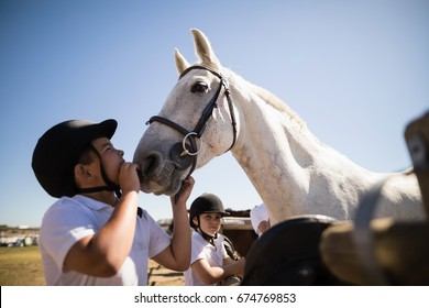Boy kissing the white horse in the ranch on a sunny day