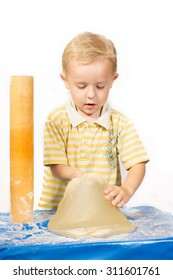 Boy knead the dough with a rolling pin for a cake and tries to pick it up on a blue tablecloth