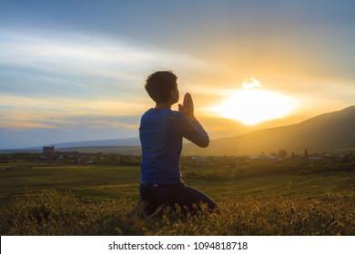 A boy kneeling and praying