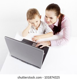 A boy and laptop. The boy and woman sit at the laptop. He learns use the laptop. She shows him what to do.