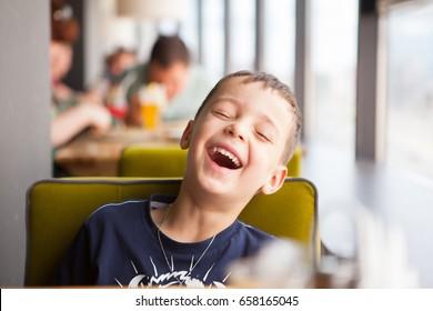 Junge lacht laut im Café
